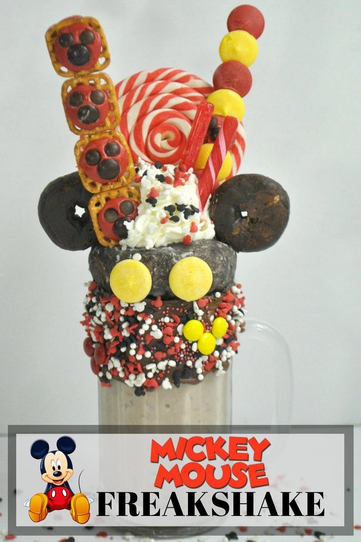This Mickey Mouse Milkshake is so much fun to make - perfect to celebrate his 90th birthday or for a party. Topped with donuts, candy and pretzels, this Mickey freak shake will be a delicious treat. #freakshake #milkshake #disneyrecipe #disney #mikeymouse