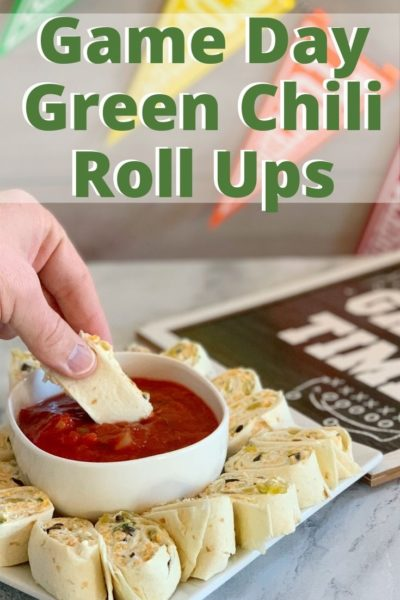 Need a big game day recipe? These green chili tortillas roll ups are full of flavor. They're a cream cheese base, with olives, green chilis and shredded cheese. Just roll up and serve with salsa! #Football #GameDayFood #PartyFood #Appetizer #TortillaRollUps #gamedayfood #superbowlfoods #superbowlappetizers