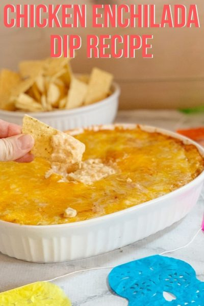 You won't be able to stop eating this Chicken Enchilada Dip recipe! Everyone asks for it at parties because it's such an easy appetizer that tastes delicious. It's cheesy, delicious and just a bit of kick. #EnchiladaDip #EasyAppetizer #SuperBowlRecipe #SuperBowlAppetizer #DipRecipe #AppetizerRecipes #MexicanDip #ChickenEnchiladas