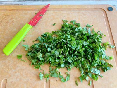 Chopping fresh basil for tomato soup