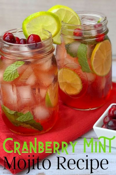 This festive Cranberry Mojito recipe is the perfect Christmas cocktail! It's muddled mint, cranberries, light rum, sugar and soda water with lime. The red and green coloring makes it perfect for the holiday season. #CranberryRecipe #CranberryCocktail #Mojito #ChristmasCocktail #ChristmasCocktailRecipes