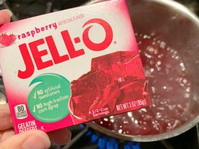 Adding raspberry gelatin to the juice mixture