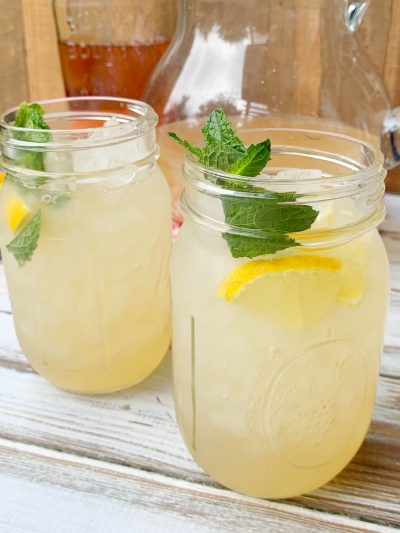 Adding lemon wedges and mint to finish bourbon spiked lemonade cocktail
